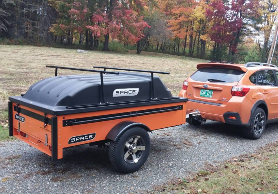 orange vehicle pulling orange space trailer